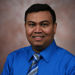 A smiling man in a blue shirt and tie
